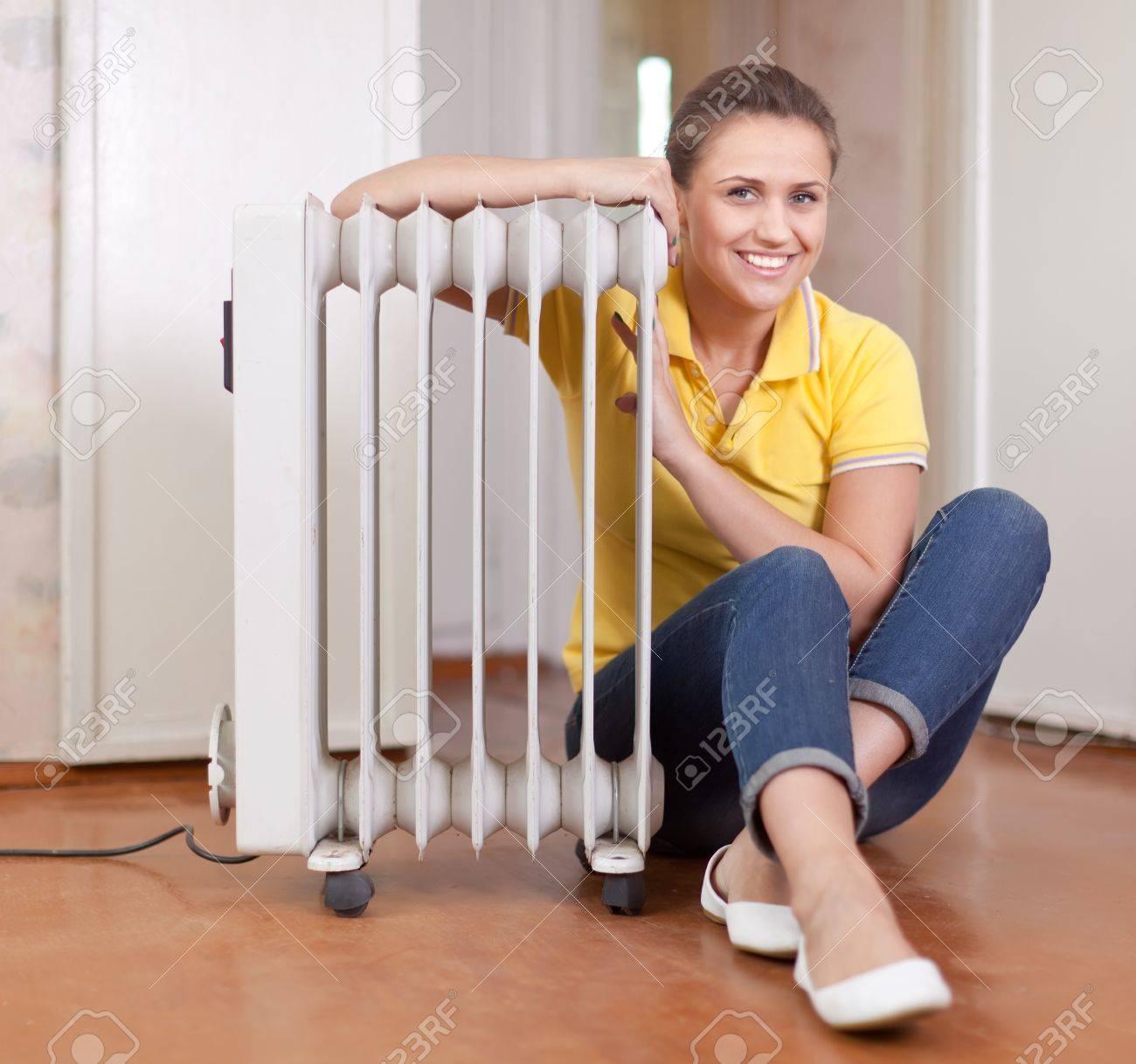 smiling woman  near warm radiator  in home Stock Photo - 15628071