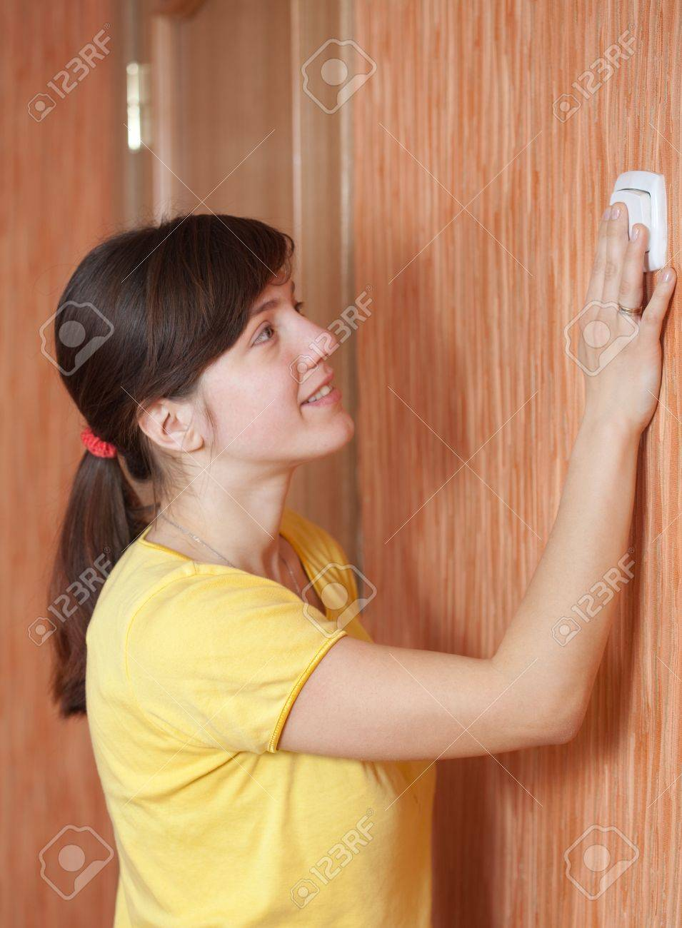 Young woman turning off the light-switch in home Stock Photo - 15870364