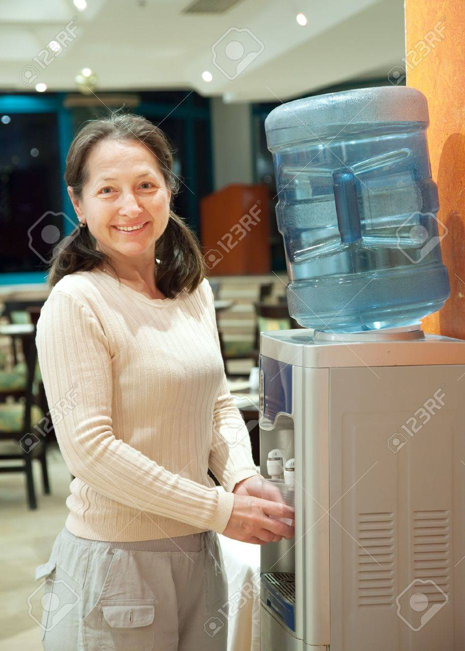 Woman pours   water from water cooler Stock Photo - 15929956