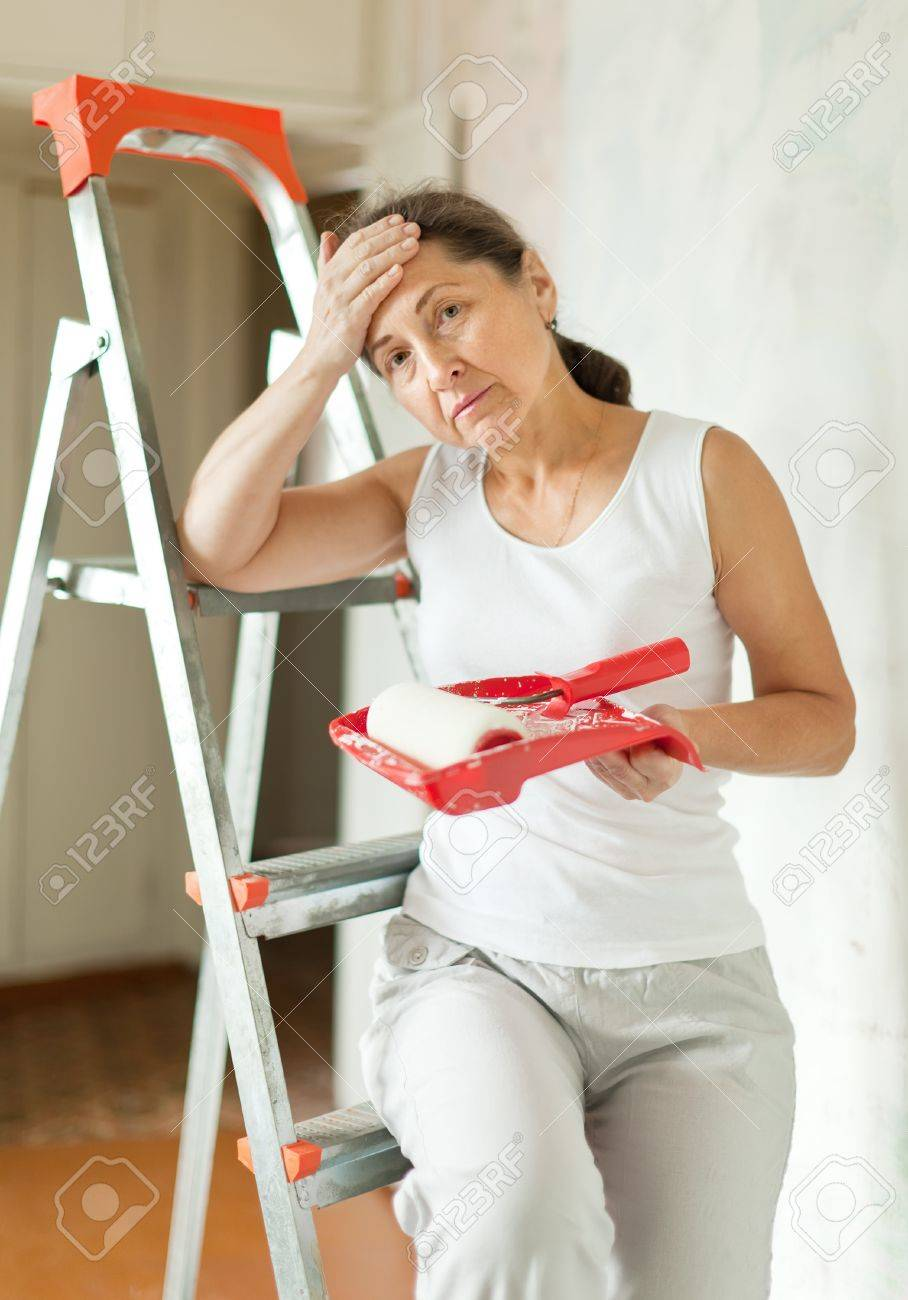 weariness mature woman makes repairs at home Stock Photo - 15940316