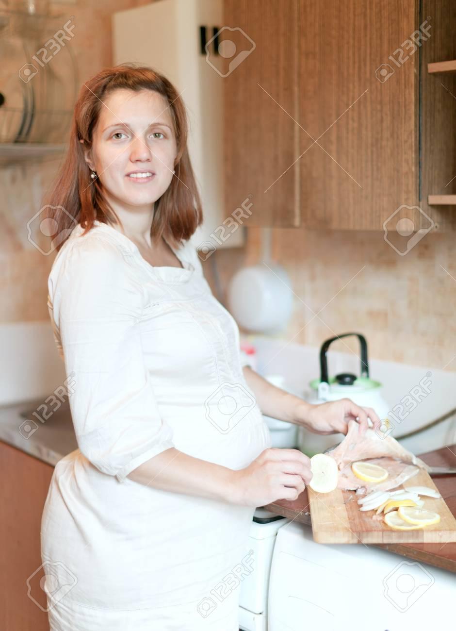 pregnant woman cooks salmon in the kitchen Stock Photo - 15978220