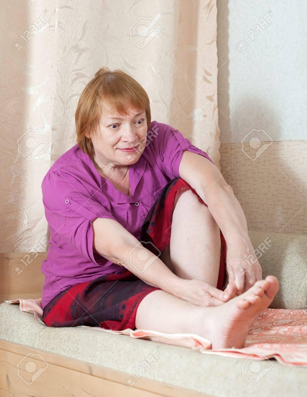 Mature woman looks at her toenails Stock Photo - 16243419