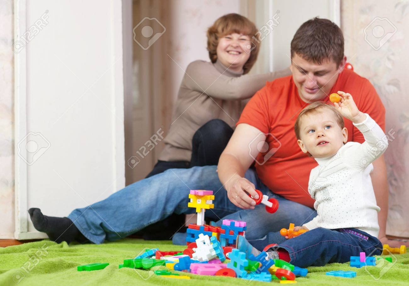 Happy parents and child plays with meccano set in home Stock Photo - 16274393