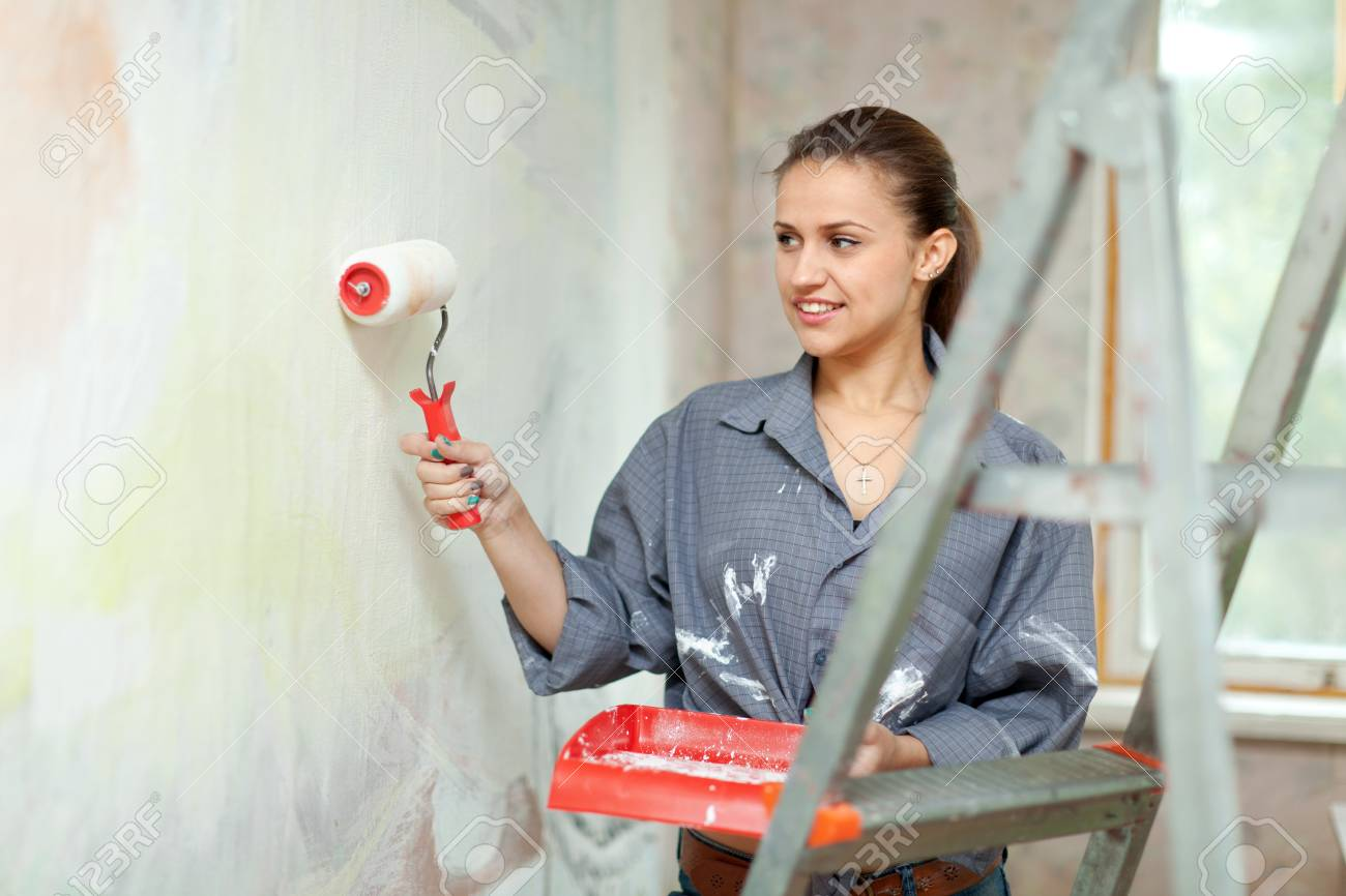 Happy woman paints wall with roller at home Stock Photo - 16516636