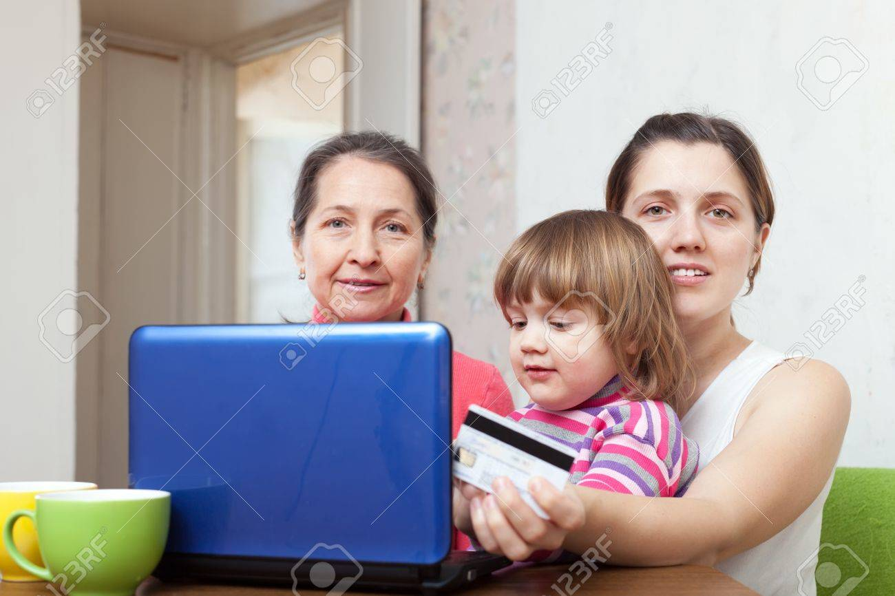 Two women and child shopping in internet from home, using laptop and paying with credit card Stock Photo - 16862829
