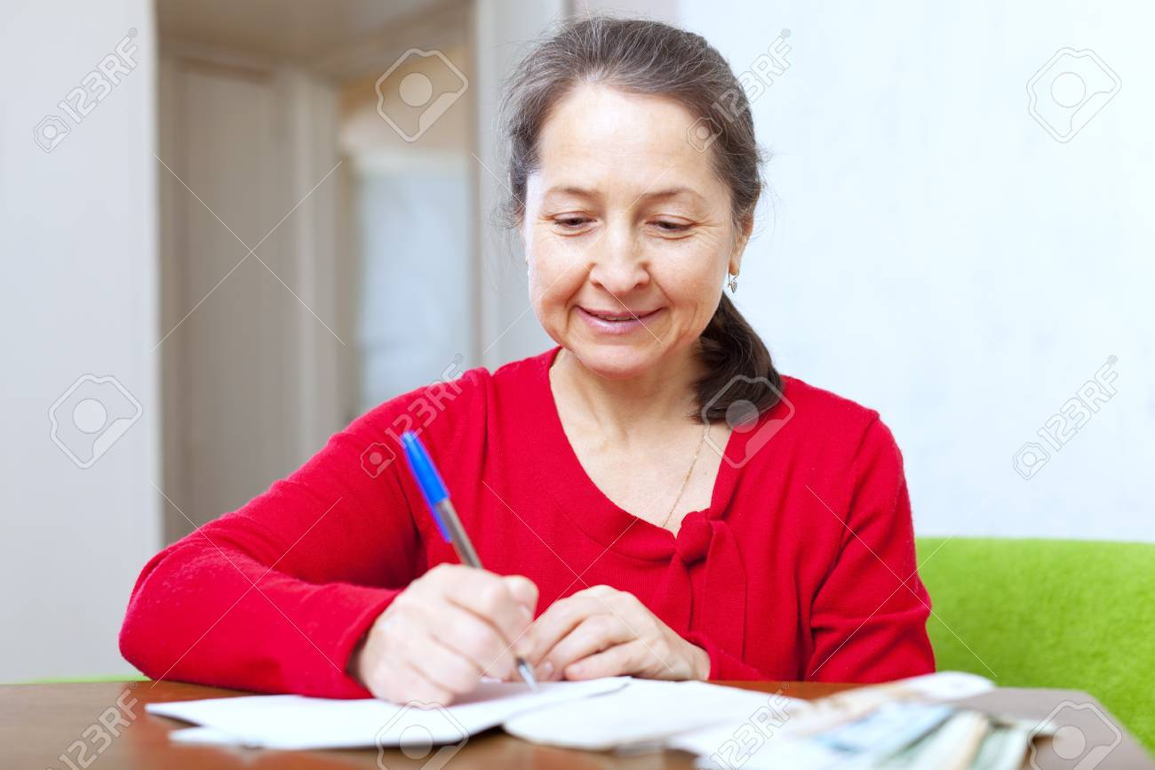 mature woman fills in  documents at home Stock Photo - 16884537