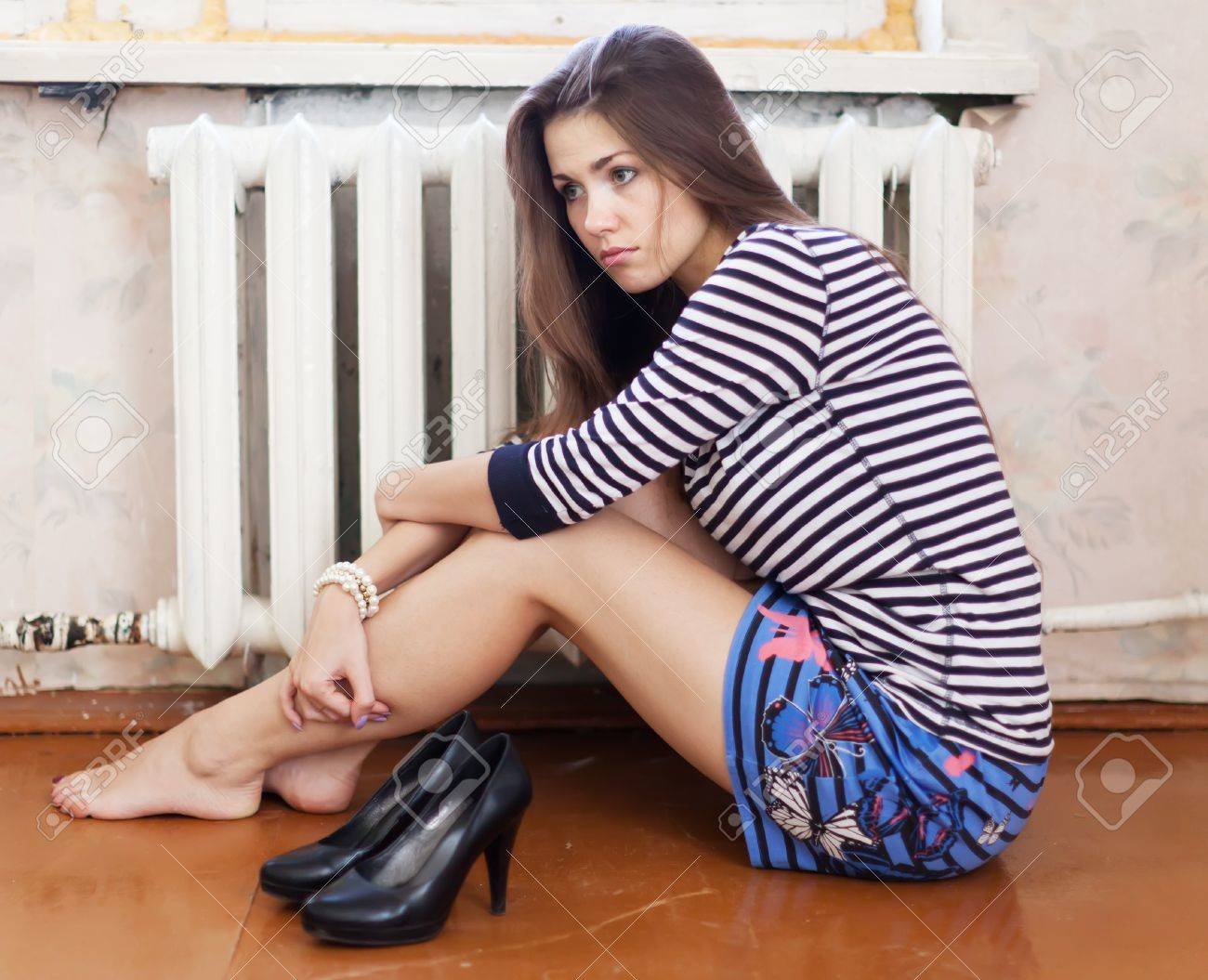 Lonely girl sitting on the floor in the corner Stock Photo - 16902120