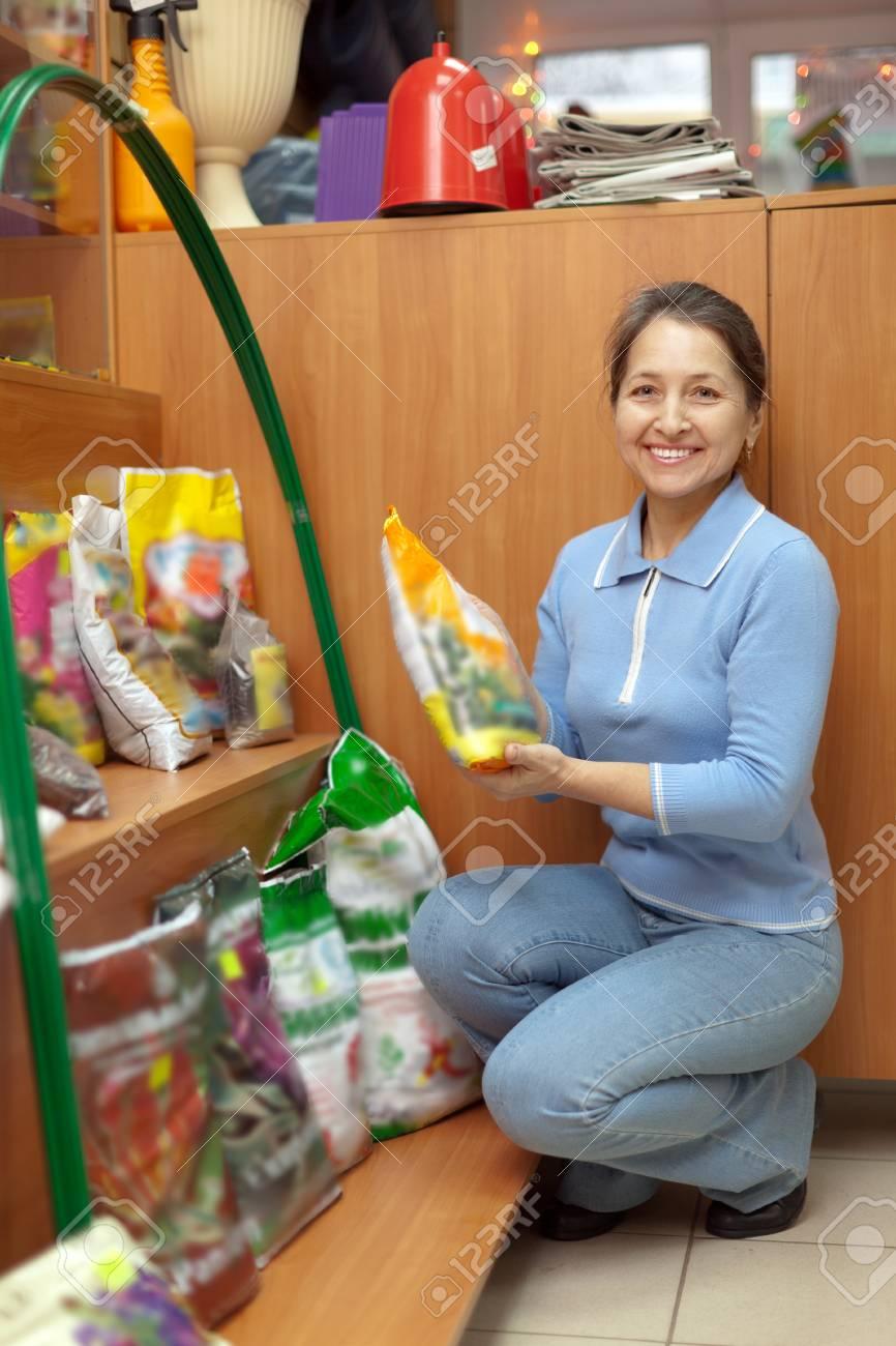Smiling mature woman chooses fertilizers at garden shop Stock Photo - 16949238