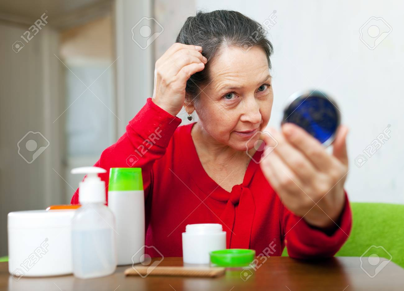 Mature woman stares on grizzled hair in mirror at home Stock Photo - 17230729