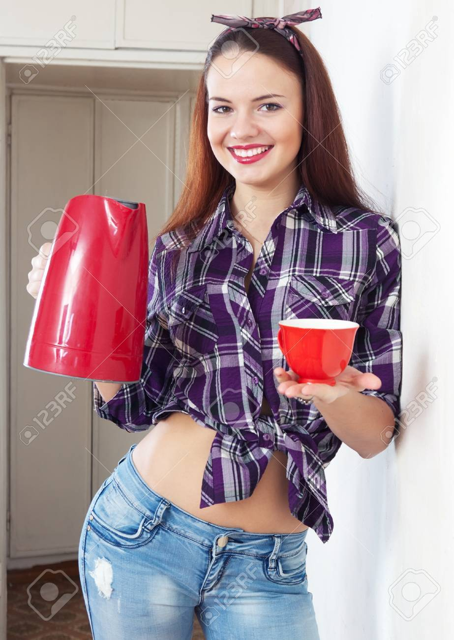 Portrait of happy pretty housewife with red kettle and cup at home interior Stock Photo - 17567079