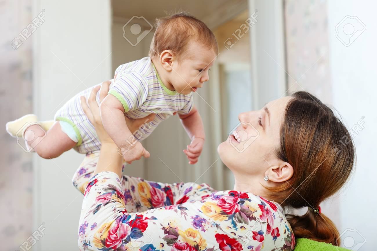 Happy mother with her baby over home interior background Stock Photo - 17592482