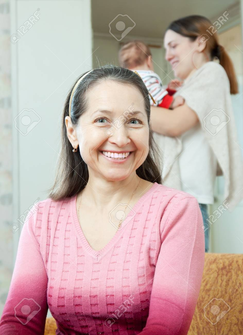 Portrait of happy mature woman against young mother with little baby at home interior. Focus on  grandmother Stock Photo - 17592512