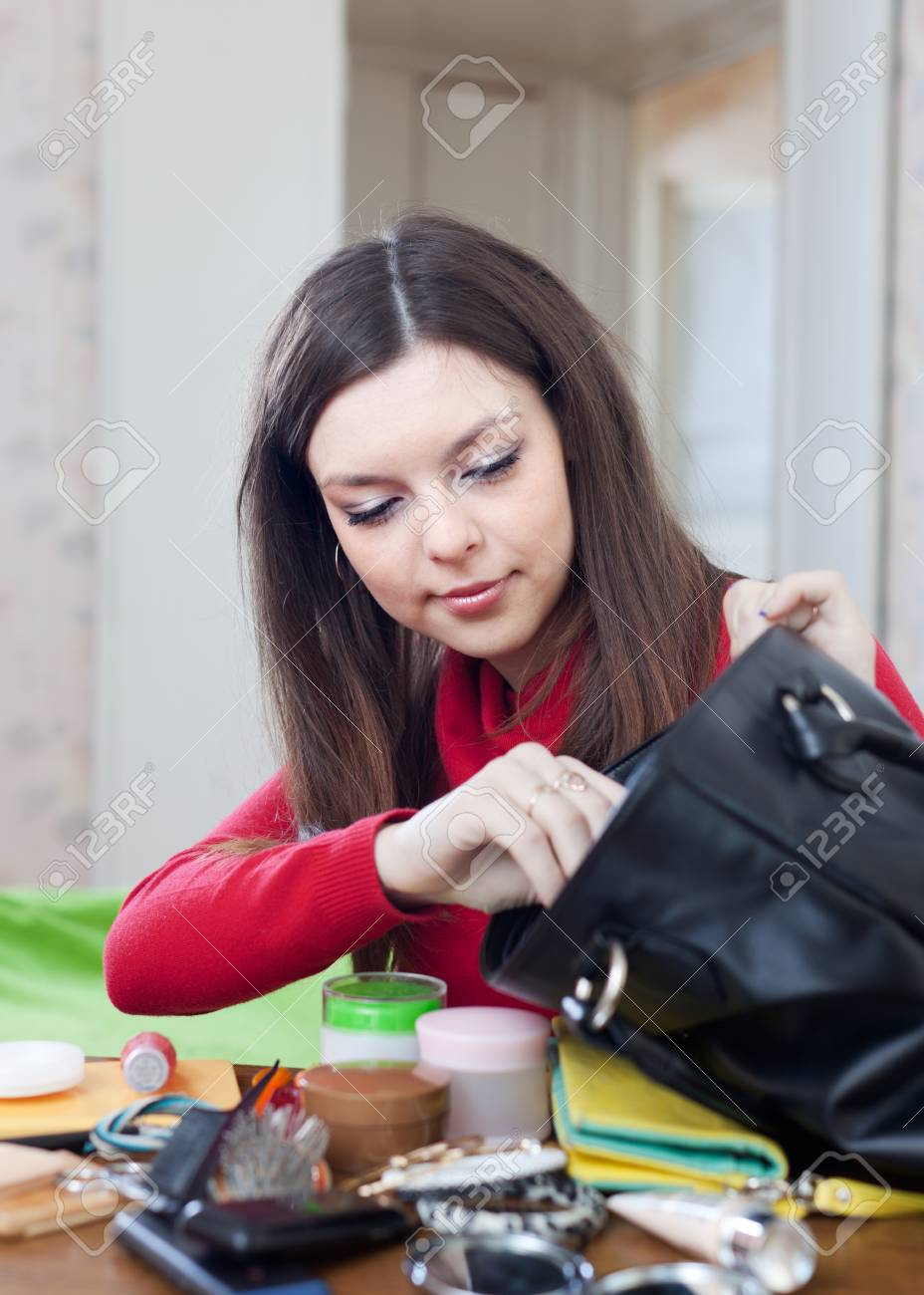 Young woman can not finding anything in her purse at table Stock Photo - 17878208