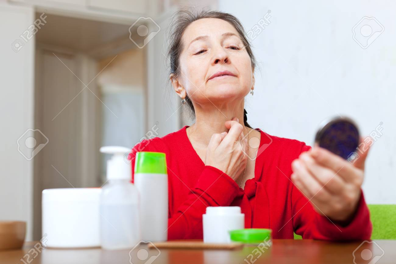 Mature woman stares on neck in mirro Stock Photo - 18291647