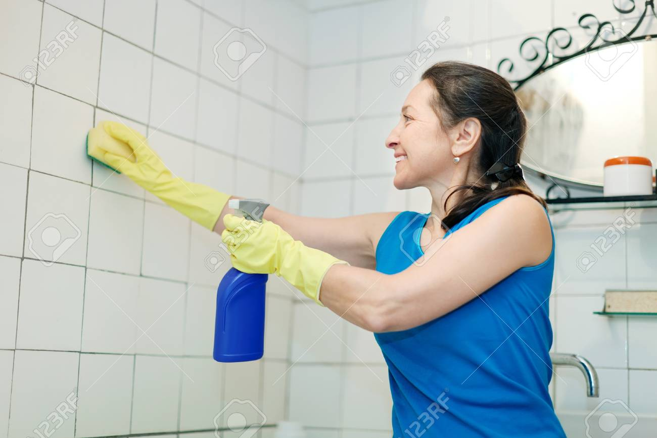 Smiling mature woman cleans tile in bathroom at home stock photo