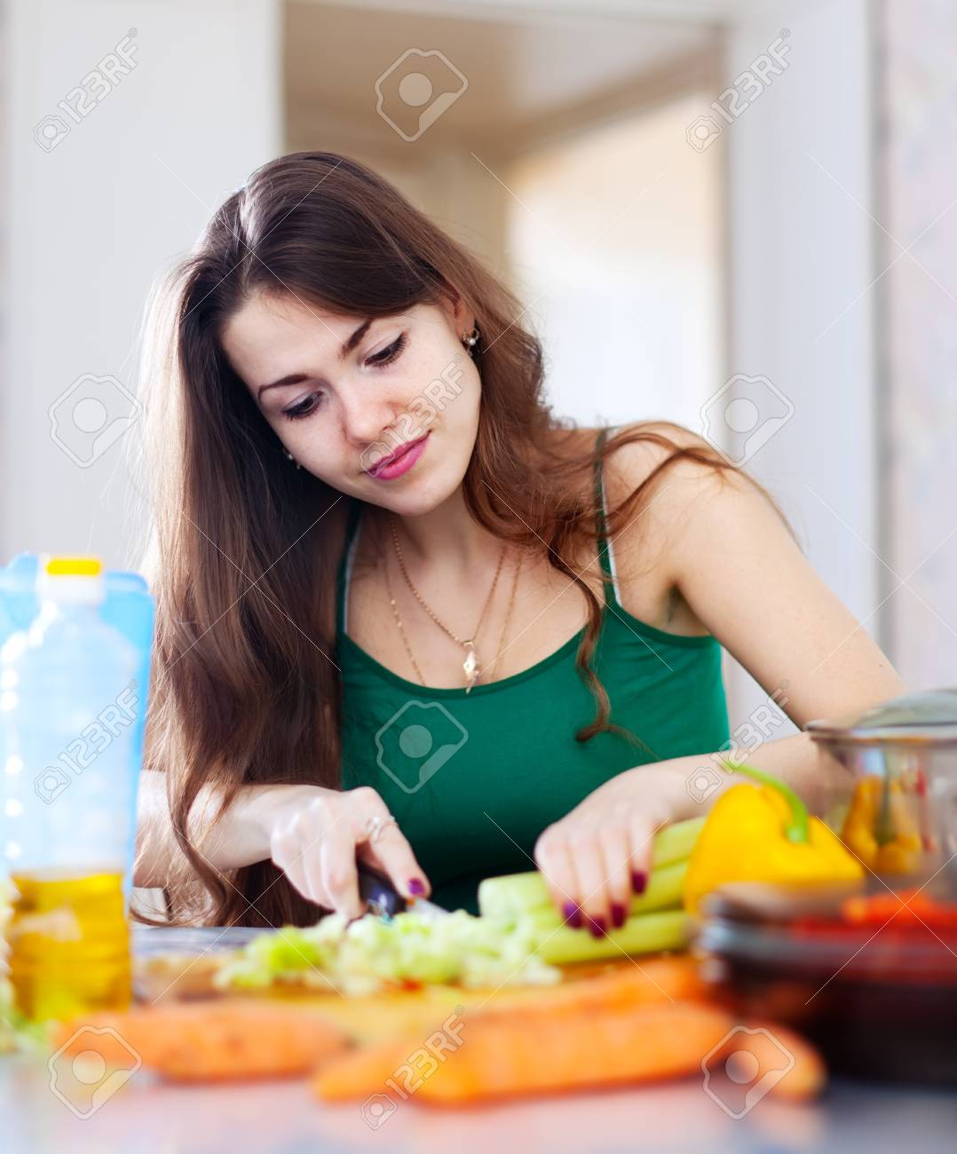 beautiful woman cutting green celery at her kitchen at home Stock Photo - 18343983