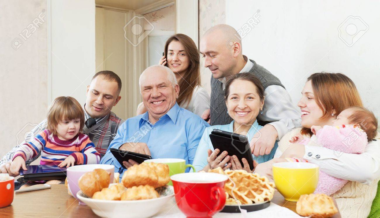 Portrait of happy multigeneration family uses electronic devices over tea Stock Photo - 18359664