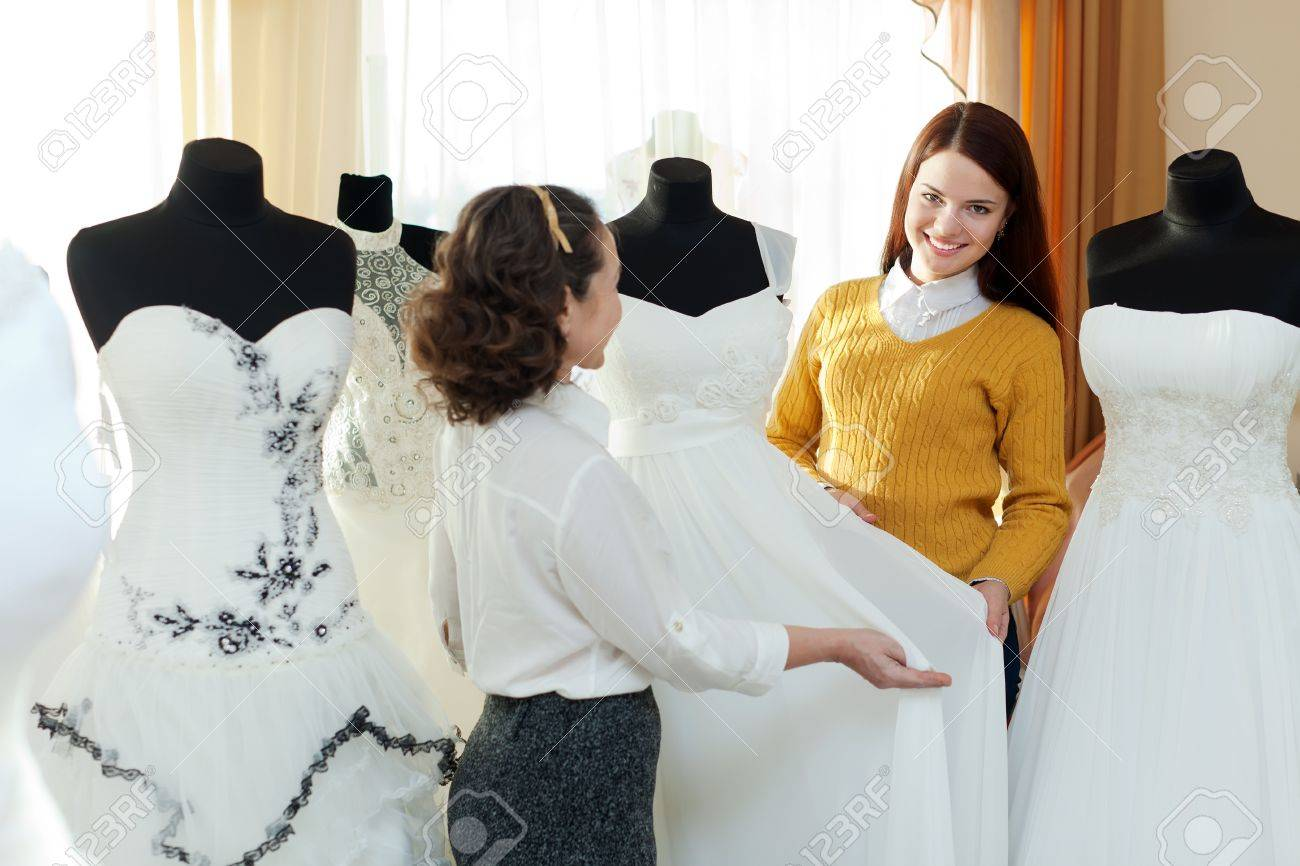 saleswoman helps girl chooses white bridal outfit at shop of wedding fashion Stock Photo - 18493267