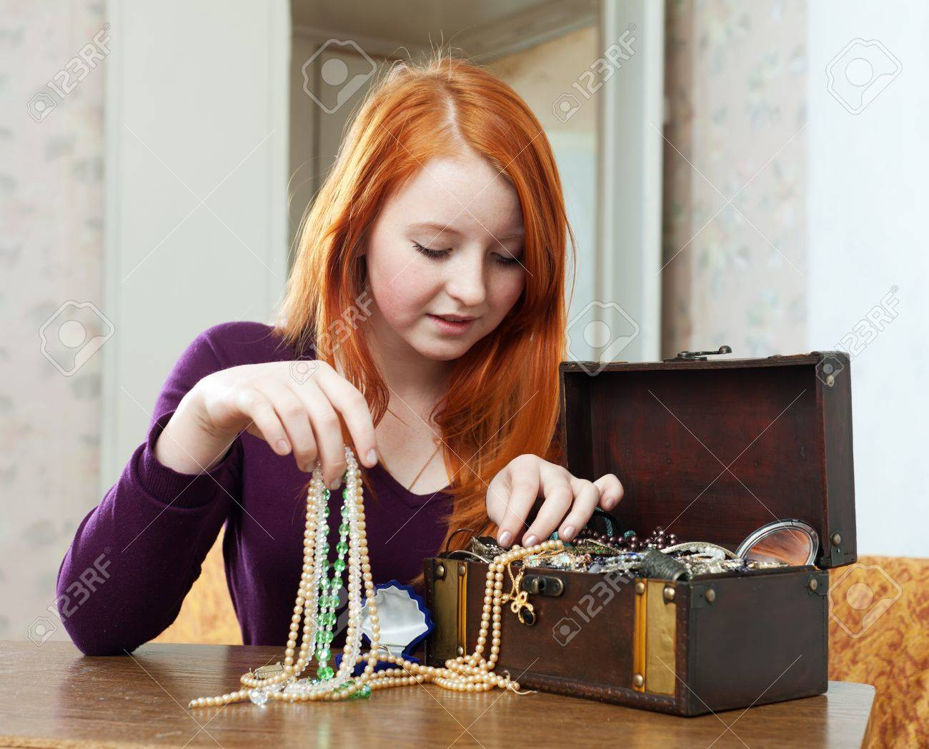 Stock Photo - teen girl chooses jewelry in treasure chest