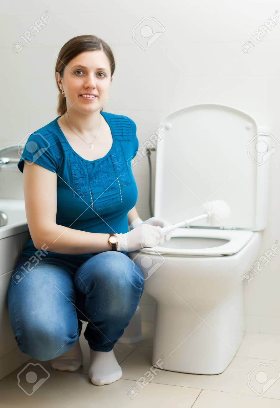 Smiling housewife cleaning toilet bowl with brush in bathroom Stock Photo - 19523115