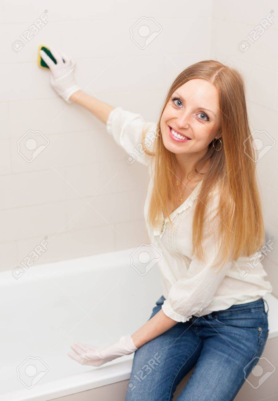 Positive long-haired woman cleaning tile with sponge in bathroom at home Stock Photo - 19803261