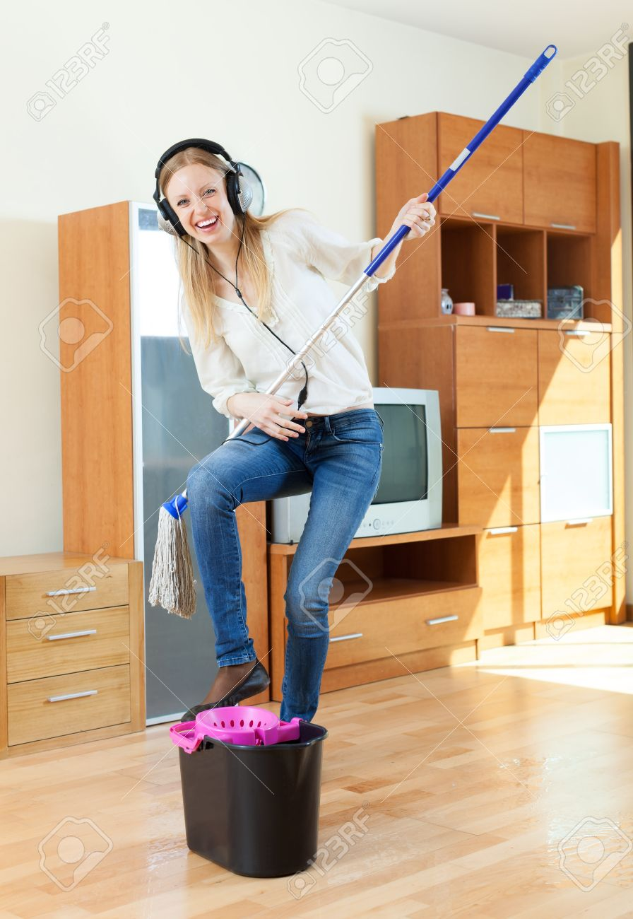 Happy housewife in headphones washing floor with mop in living room at home Stock Photo - 19869584