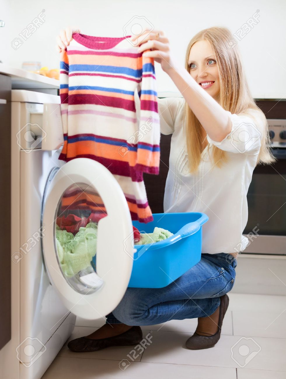 long haired woman with color clothes near washing machine at