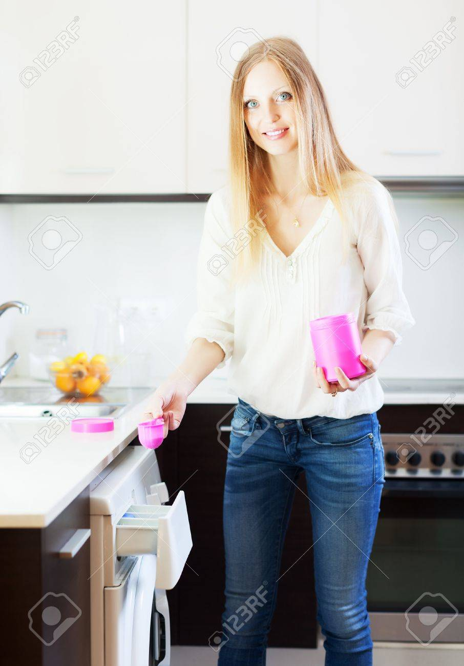 Happy blonde  woman doing laundry with detergent at home Stock Photo - 21110986