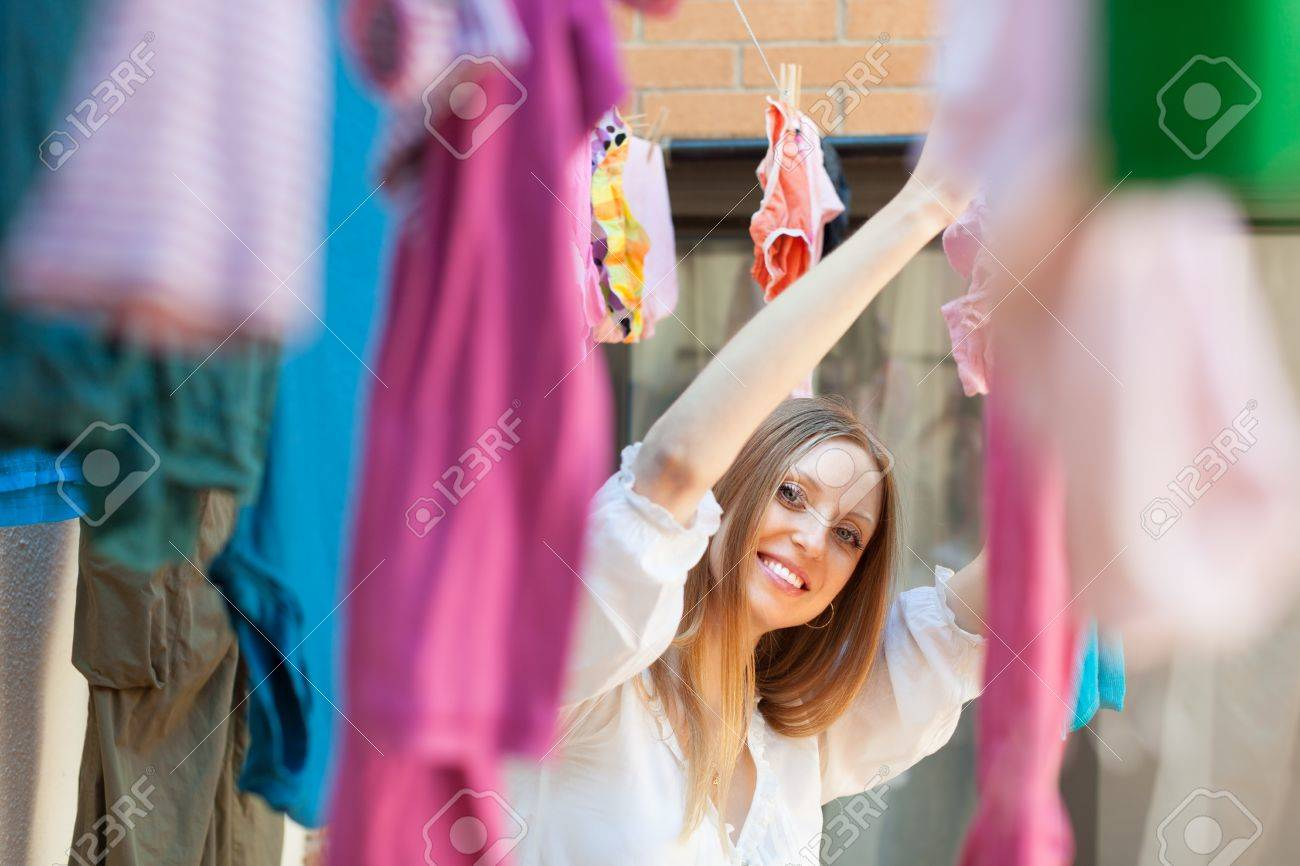 Smiling Woman Hanging Clothes To Dry On Clothes Line After Laundry