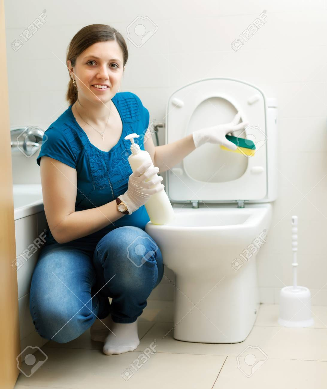 Smiling housewife cleaning toilet bowl with sponge in bathroom Stock Photo - 21111043