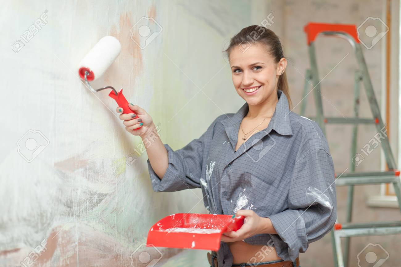 Happy girl paints wall with roller Stock Photo - 21503913