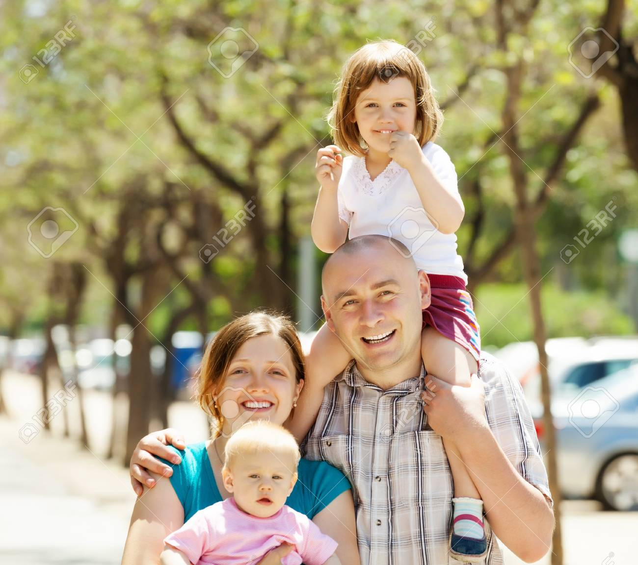 Happy couple together with children in summer street Stock Photo - 21621908