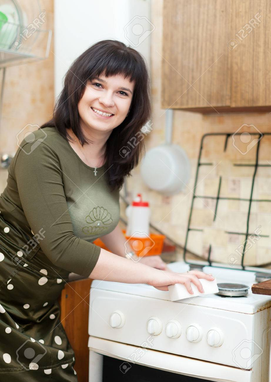 Happy housewife cleans the gas-stove with melamine sponge  at kitchen Stock Photo - 22554188