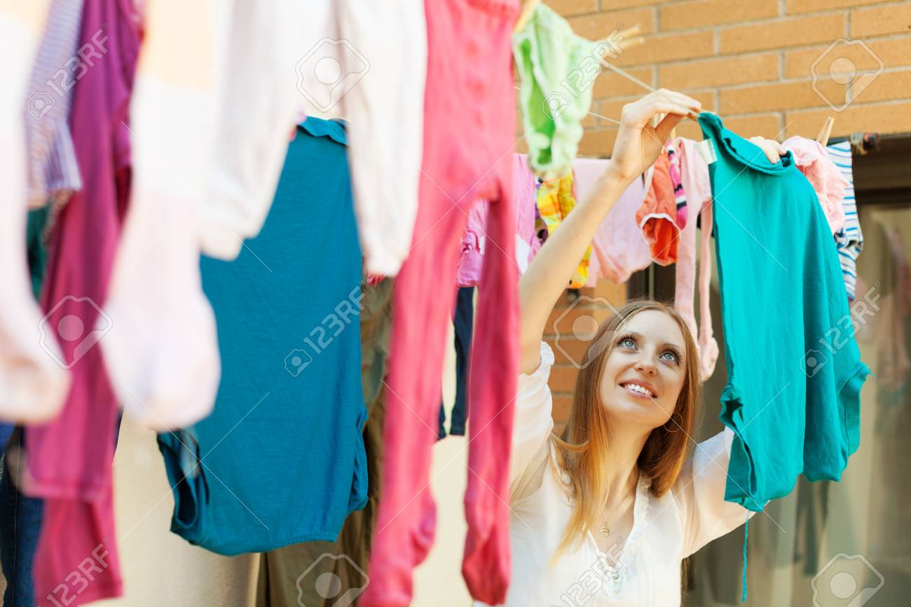 Long Haired Housewife Hanging Clothes To Dry On Clothes Line Stock