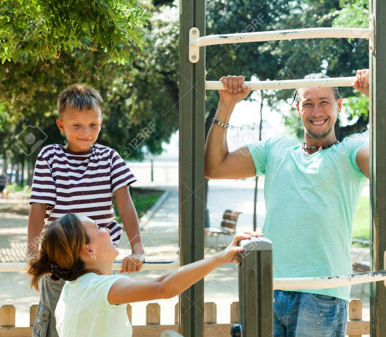 Happy couple with teenage son training on pull-up bar in sunny..