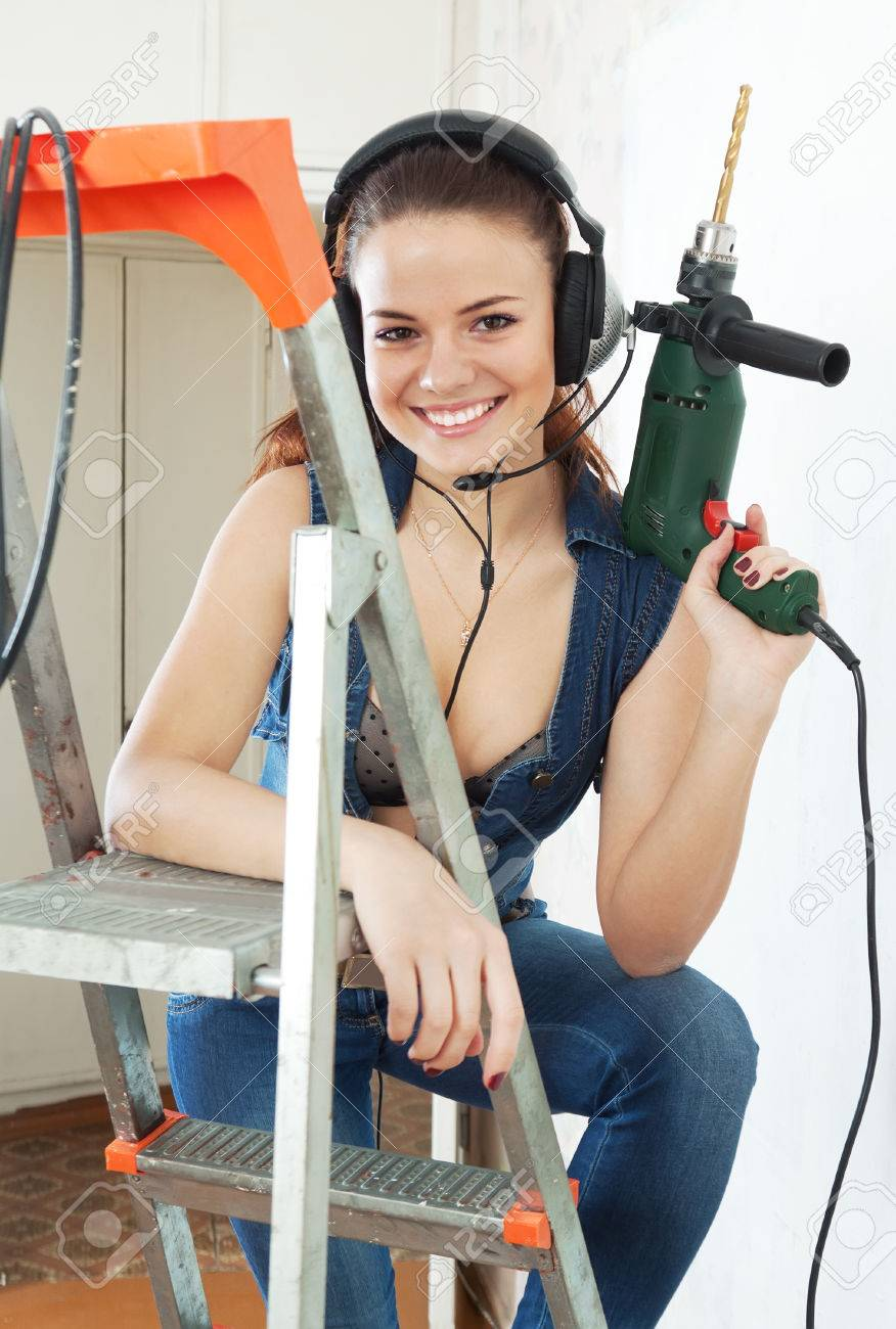 happy sexy girl in overalls with drill makes repairs at home stock