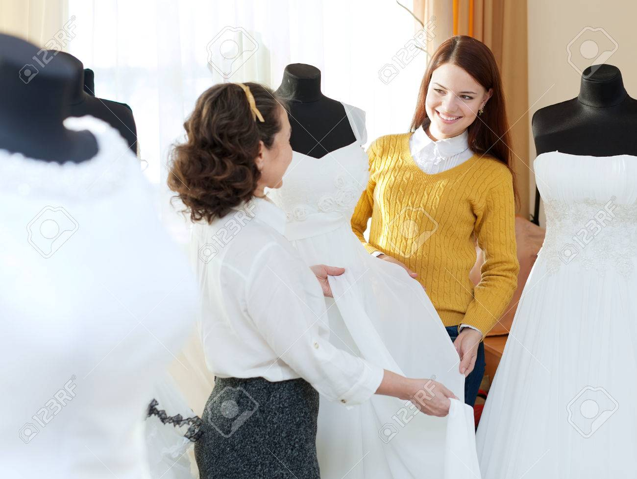 Pretty Bride Chooses Bridal Dress At Wedding Store Shop Consultant Stock Photo Picture And Royalty Free Image Image 24282983
