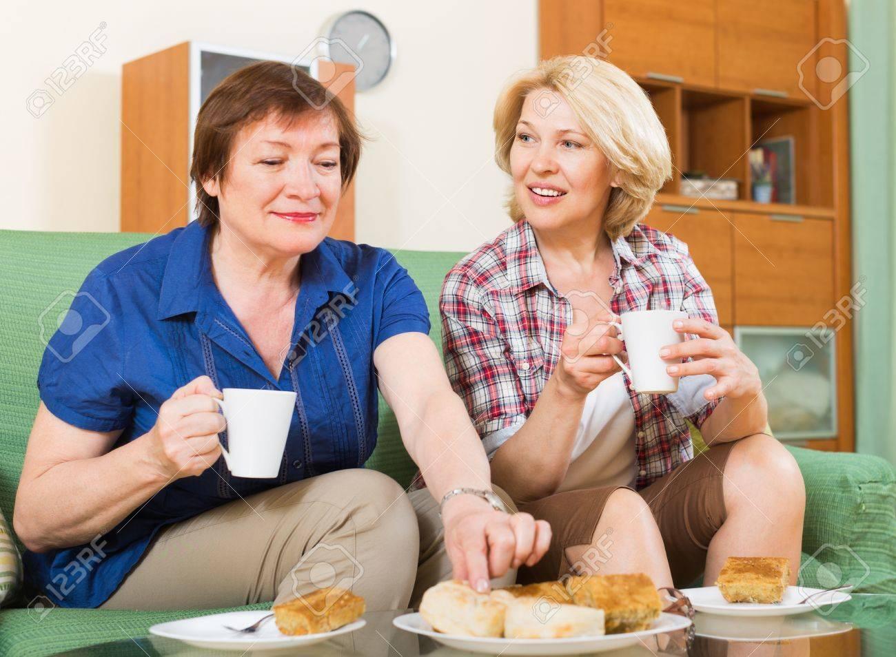 Amigas Maduras dos amigas maduras positivas bebiendo té y cotilleo en casa