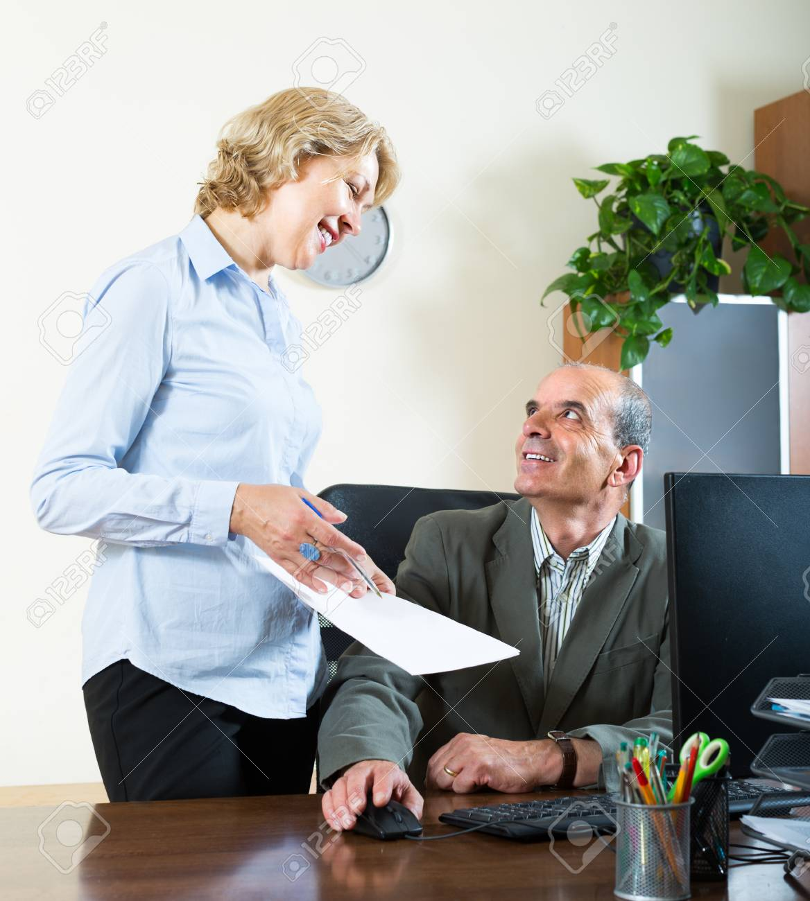elderly chief talking with smiling mature female secretary in