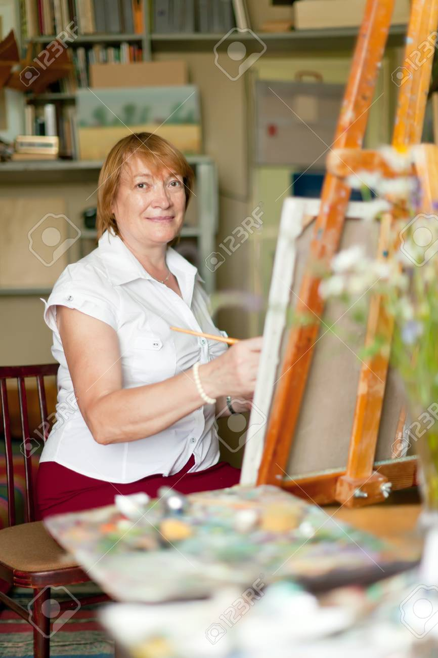 Female artist paints a picture on canvas with oil paints Stock Photo - 30930567