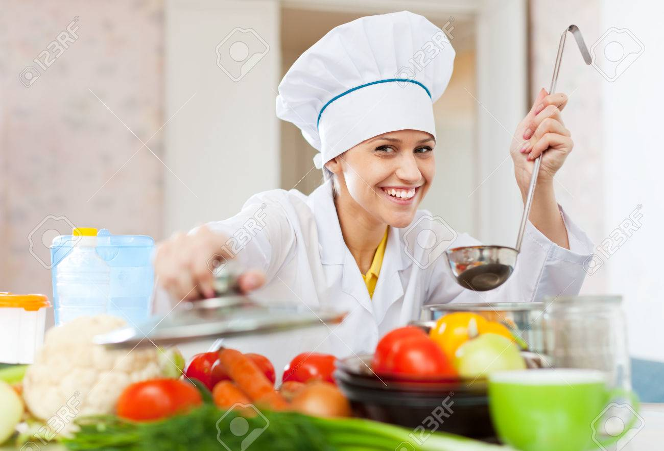 happy professional cook in white workwear works in commercial