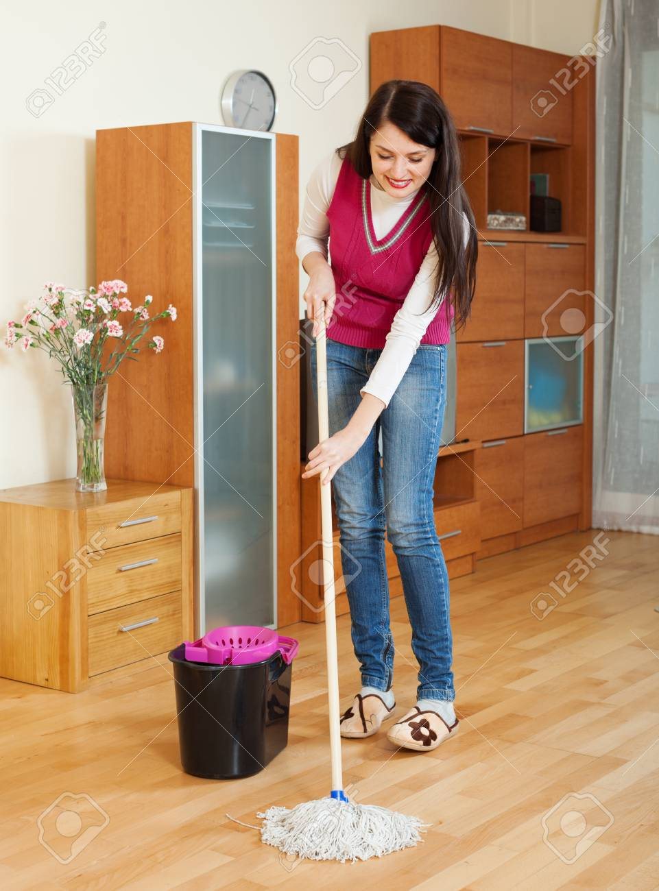 Sourire brunette femme laver le sol avec une vadrouille à la maison