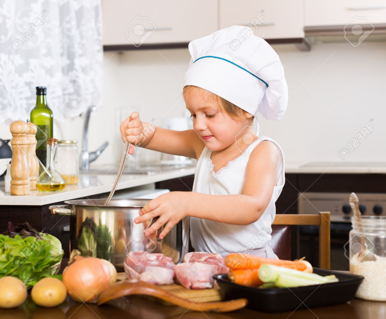 Home Kitchen Cooking cute baby girl in chef's hat cooking food at home kitchen stock