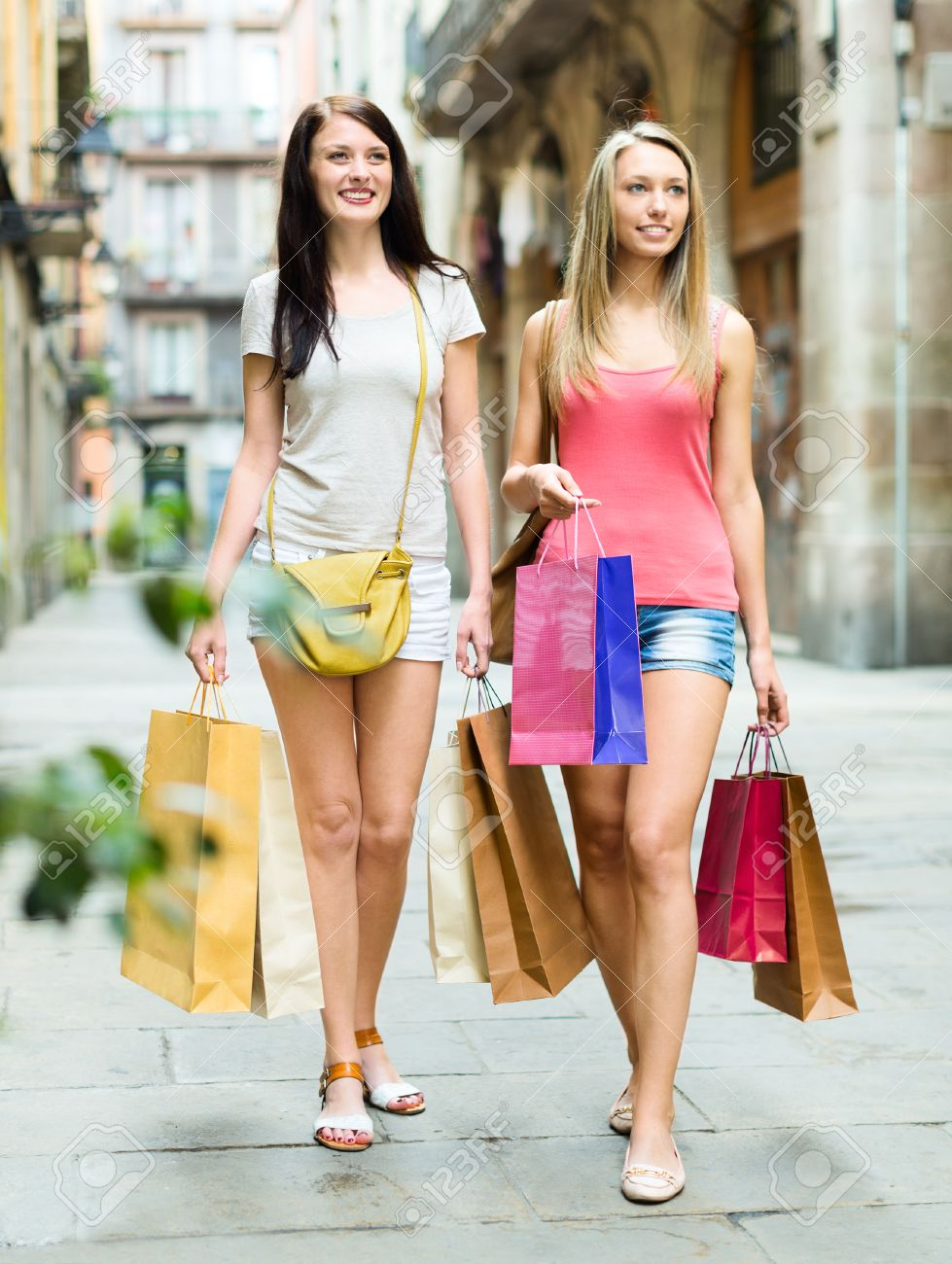 two nice girls with shopping bags walking on city street stock photo