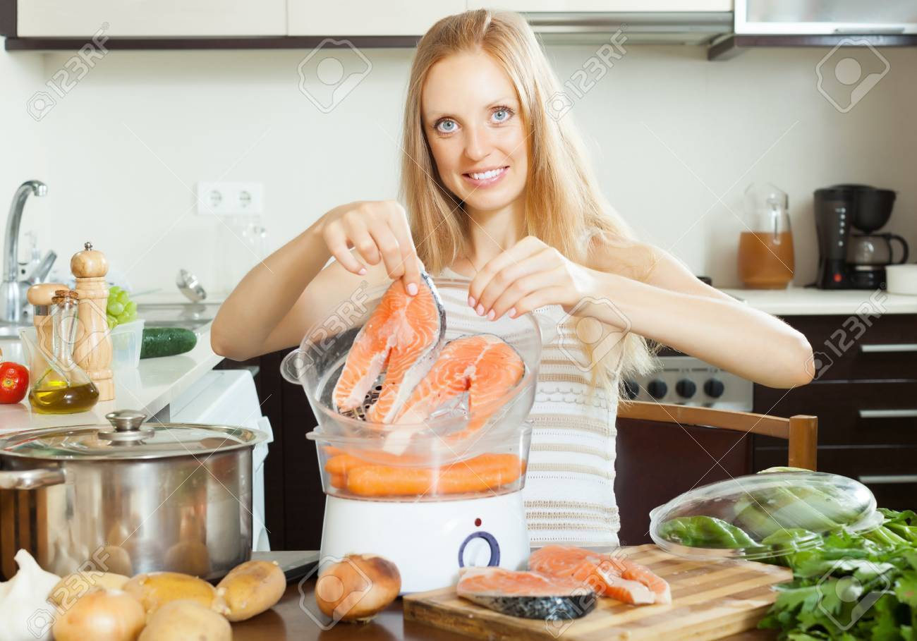 Stock Photo Woman Cooking Vegetables And Salmon In Electric Steamer At Home  Woman Cooking Vegetables And