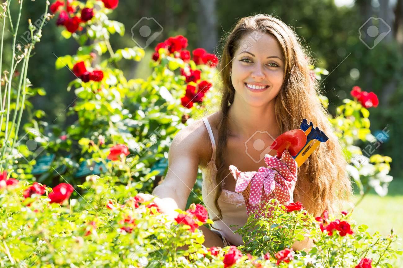 Mujer feliz que trabaja en las plantas de rosas en el jardín de verano