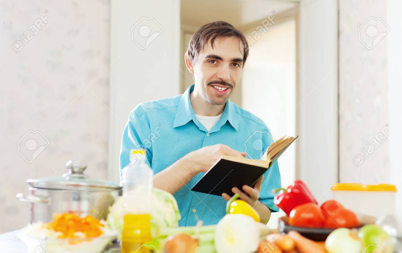 Adult Man Doing Veggy Lunch With Cookbook At Kitchen Stock Photo ...