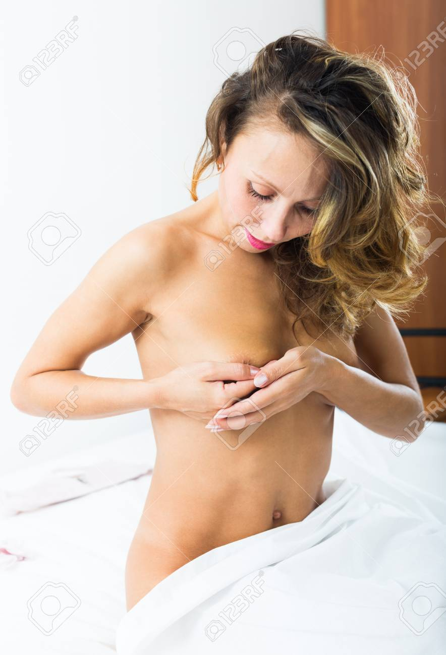 Nude middle-aged woman covering bosom with hands in bedroom Stock Photo -  37158626