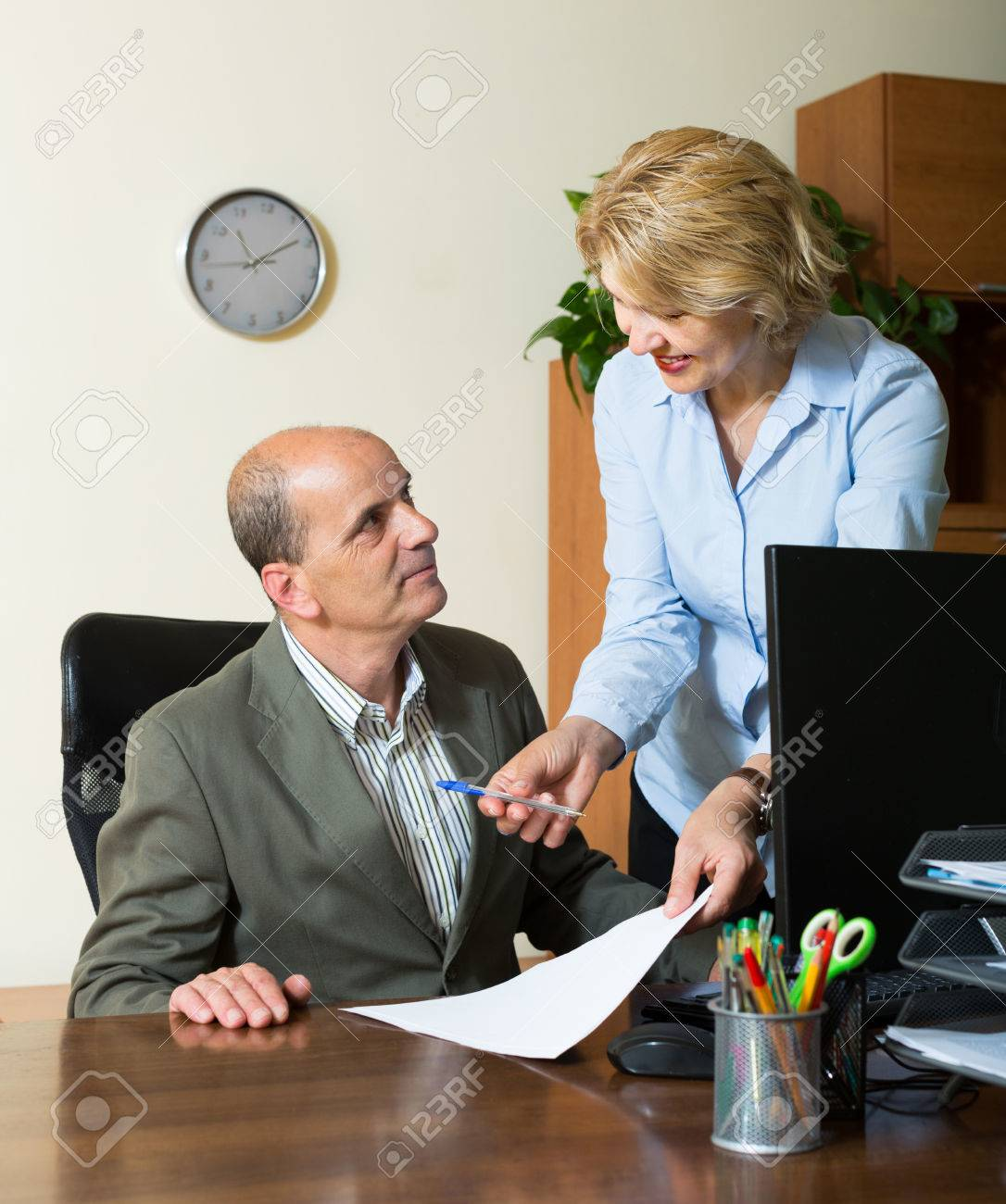 elderly chief with smiling mature female secretary in office stock