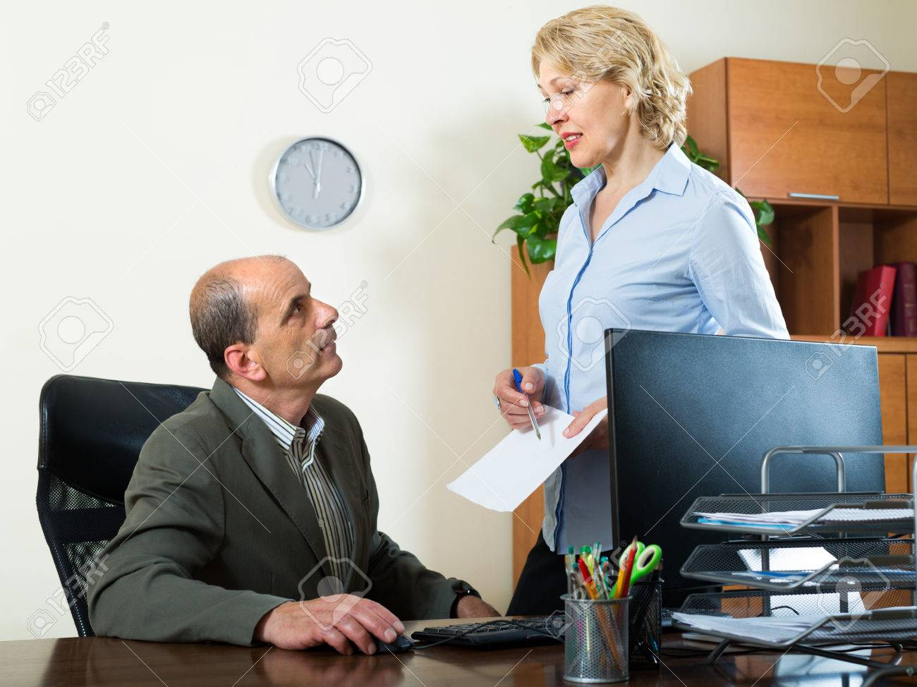 aged chief listening mature female secretary in office stock photo